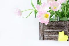 Букет розовых тюльпанов в деревянной коробке и желтом бумажном сердце на белой предпосылке стоковая фотография rf