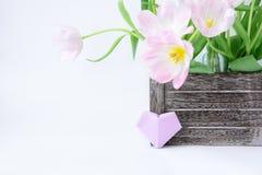 Букет розовых тюльпанов в деревянной коробке и сердце бумаги сливы на белой предпосылке стоковое изображение rf