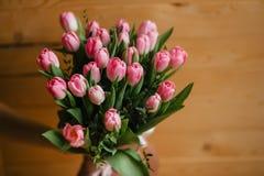 Букет розовых тюльпанов с красивым смычком на деревянной предпосылке Стоковые Фотографии RF