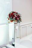 Букет роз и растительности стоит на стеклянной коробке Стоковое Фото