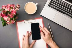 Букет роз, чашки кофе, женских рук с smartphone и компьтер-книжки на серой таблице Взгляд сверху Стоковые Фото
