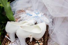 Букет свадьбы нежный белых и розовых роз и высоко-накрененных ботинок на зеленой траве в парке голубая подвязка цветка деталей шн стоковые изображения