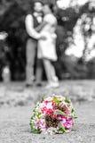 Букет свадьбы перед новобрачными соединяет предпосылку, целуя bokeh малой глубины стоковое изображение rf