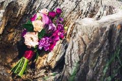 Букет свадьбы стоит около старого текстурированного пня стоковое изображение