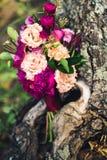 Букет свадьбы стоит около старого текстурированного пня стоковая фотография