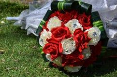 Букет свадьбы шарлаха и белых роз и белого зонтика на траве Стоковые Изображения