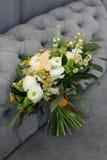 Букет свадьбы cream роз и белых пионов в деревенском стиле на предпосылке серой софы Стоковые Изображения RF