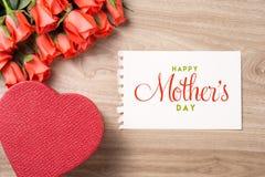 Букет свежих розовых красных роз с подарком на деревянной предпосылке Флористическое романтичное расположение с Днем матери текст Стоковое Фото