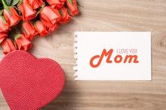 Букет свежих розовых красных роз с подарком на деревянной предпосылке Флористическое романтичное расположение с Днем матери текст Стоковая Фотография RF