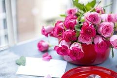 Букет свежих розовых роз, в лотке красного литого железа, на серой каменной предпосылке около окна качество изображения габарита  Стоковое Фото