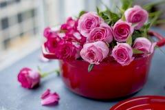 Букет свежих розовых роз, в лотке красного литого железа, на серой каменной предпосылке около окна качество изображения габарита  Стоковые Фото