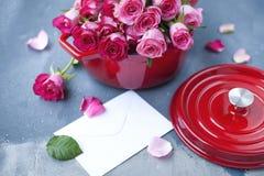 Букет свежих розовых роз, в лотке красного литого железа, на серой каменной предпосылке около окна качество изображения габарита  Стоковая Фотография