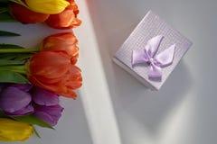 Букет свежих тюльпанов загоренных лучем солнца и подарочной коробки лежа на деревянном столе Стоковая Фотография