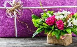 Букет свежих цветков и подарочной коробки на старом деревянном столе Стоковая Фотография