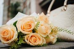 Букет светлоых-желт роз на предпосылке белой сумки стоковые фотографии rf