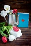 Букет тюльпанов, блокнота с сердцем, бака кофе и белой подарочной коробки Стоковые Фото