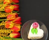 Букет тюльпанов на таблице с чашкой чаю и сердцем сформировал торт на темной предпосылке стоковая фотография