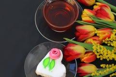 Букет тюльпанов на таблице с чашкой чаю и тортом в форме сердца стоковое фото
