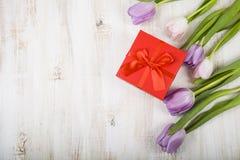 Букет тюльпанов и подарка на деревянной предпосылке Стоковые Изображения