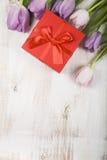Букет тюльпанов и подарка на деревянной предпосылке Стоковая Фотография