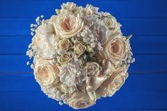 Букет цвета слоновой кости свадьбы роз на голубой деревянной предпосылке, цветочной композиции в пастельном цвете, торжестве Стоковая Фотография RF