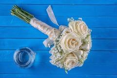 Букет цвета слоновой кости свадьбы роз на голубой деревянной предпосылке, цветочной композиции в пастельном цвете, торжестве Стоковое Изображение RF