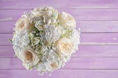 Букет цвета слоновой кости свадьбы роз на розовой деревянной предпосылке, цветочной композиции в пастельном цвете, торжестве Стоковые Фотографии RF