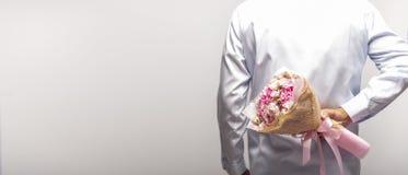 Букет цветка удерживания человека за его задней частью на белой предпосылке стоковые фото