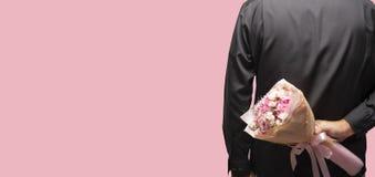 Букет цветка удерживания человека за его задней частью на розовой предпосылке стоковые фотографии rf
