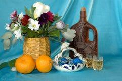 Букет цветков, апельсинов, бутылки вина, стекел, вазы Стоковое фото RF