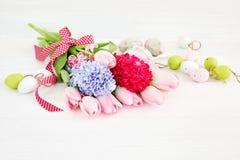 Букет цветков весны и декоративных пасхальных яя на белой деревянной предпосылке сфокусируйте мягко Стоковое фото RF