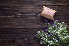 Букет цветков и подарочной коробки на темной деревянной предпосылке Курорт Стоковое Изображение