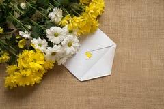 Букет camomiles на предпосылке мешковины с листьями и бумагой стоковая фотография