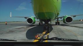 Буксировка хвостом вперед пассажирского самолета на авиапорте в ангаре Нос самолета, посадочное устройство и конец тележки отбукс акции видеоматериалы
