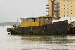 Буксир в процессе быть преобразованным к прогулочному судну связанному вверх на quayside в гавани Hythe на воде Саутгемптона на t Стоковое Изображение