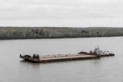 Буксир нажимает баржу вверх по реке стоковая фотография rf