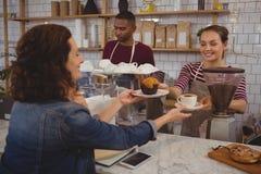 Булочка и кофе сервировки предпринимателя к клиенту Стоковое Фото