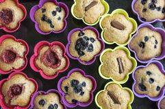 Булочки банана с шоколадом, голубиками, гайками и изюминками в прессформах силикона Стоковая Фотография RF