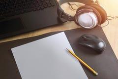 Бумага компьтер-книжки наушников на предпосылке деревянного стола Стоковая Фотография