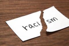 Бумага написанная как расизм сорвана на древесине Концепция упразднения расовой дискриминации стоковое фото rf