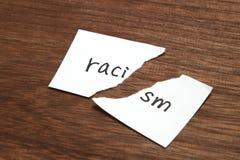 Бумага написанная как расизм сорвана на древесине Концепция упразднения расовой дискриминации стоковые фотографии rf