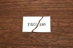 Бумага написанная как расизм сорвана на древесине Концепция упразднения расовой дискриминации стоковое изображение