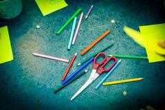 Бумага ножниц карандашей на таблице Тонизированная синь Стоковые Фото