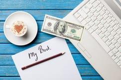 Бумага, доллар, кофе и компьтер-книжка лежа на таблице Стоковая Фотография