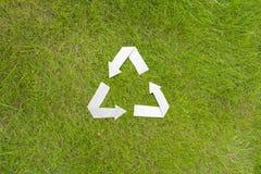 Бумага рециркулирует символ на зеленой траве Стоковое Изображение RF