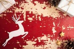 Бумага рождества отрезала оленей на винтажном деревянном фоне Стоковые Изображения