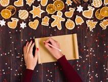 Бумага ручки удерживания руки женщины пустая для выпечки пряника рождества рецепта Стоковое Изображение