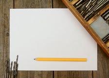 Бумага с карандашем и коробкой, сверлами на деревянном Стоковая Фотография