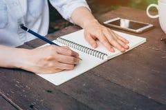 Бумага тетради сочинительства руки женщины битника в кофейне Стоковые Изображения RF