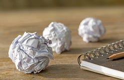 Бумага шарика с тетрадью на деревянном столе Стоковое Изображение